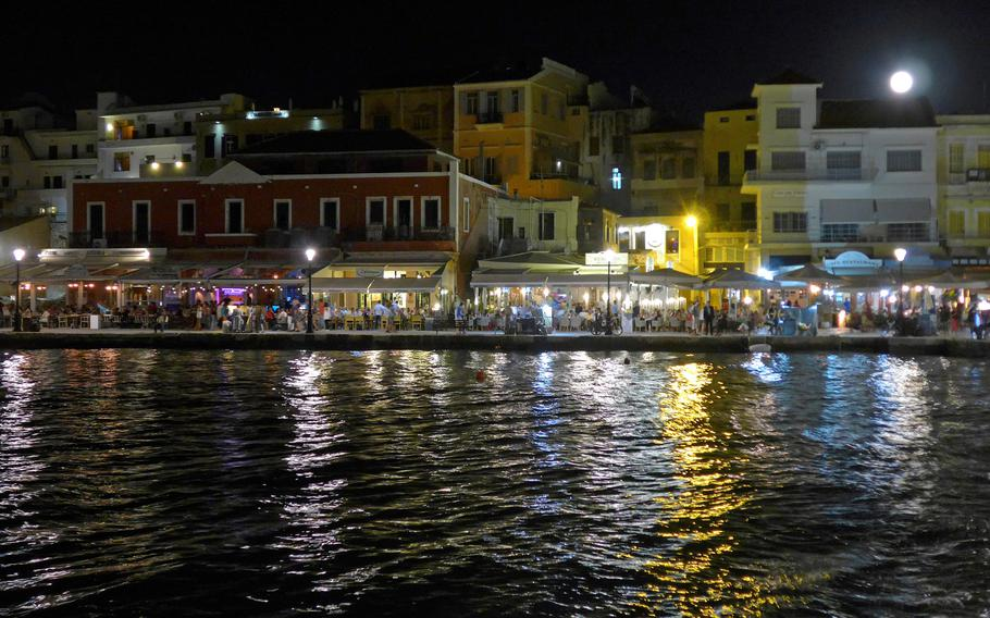A full moon rises over the houses lining Chania, Crete's Old Port. They are full of shops, restaurants and bars.