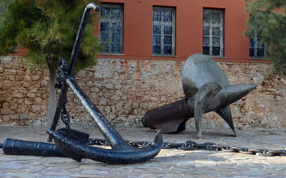 An anchor and a ship's propeller stand in front of the entrance to the Maritime Museum of Crete in Chania.