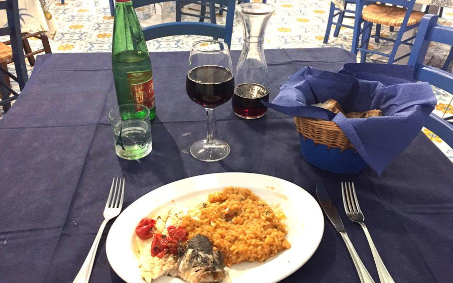 Fish and risotto served with a decanter of red house wine at Ristorante I Primi, a higher-end but popular seafood restaurant in the Posillipo neighborhood.