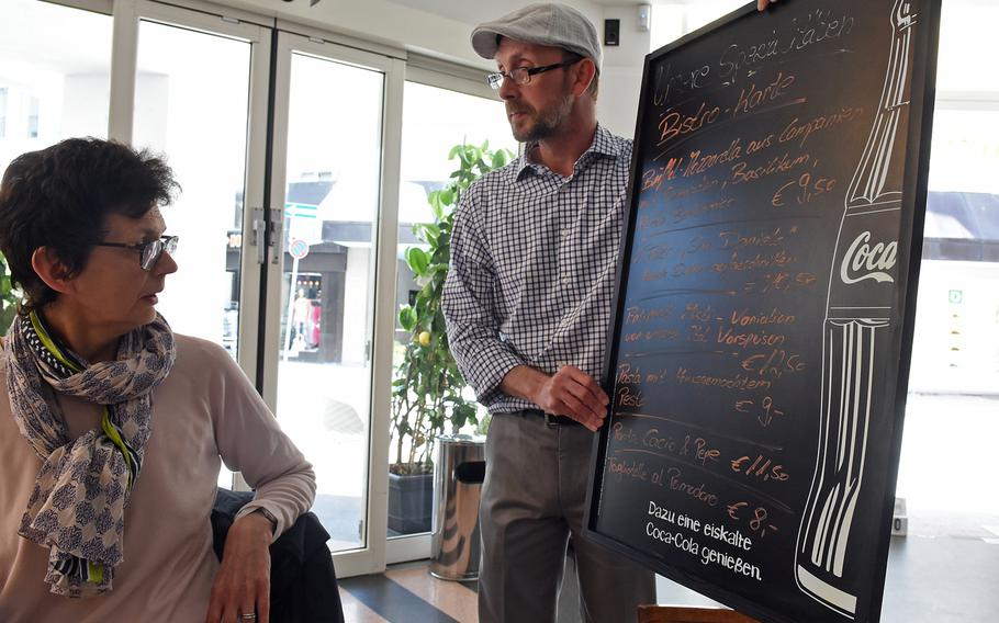 A customer looks at what's for lunch on the daily chalkboard menu at Italiano Sapori Veri in Kaiserslautern, Germany.