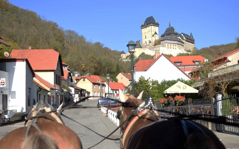 A horse-drawn carriage makes its way up a hill to reach Karlstejn Castle, the seat of Holy Roman Emperor Charles IV, in the Czech Republic.