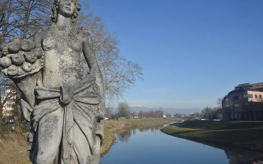 A statue on one of the two bridges to span the Monticano River in Oderzo, Italy, gazes toward the downtown area and away from the countryside and snow-topped mountains that loom in the horizon.