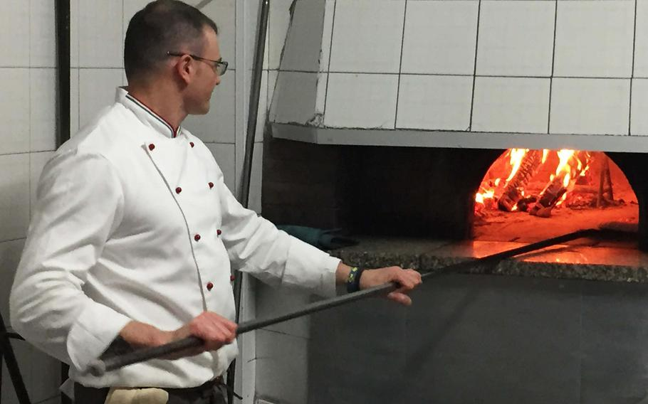 A cook bakes pizzas in a wood-fired oven at Pizzeria Trattoria Lucrino in Pozzuoli, Italy. The restaurant offers a diverse selection of pizzas and seafood at a modest price.