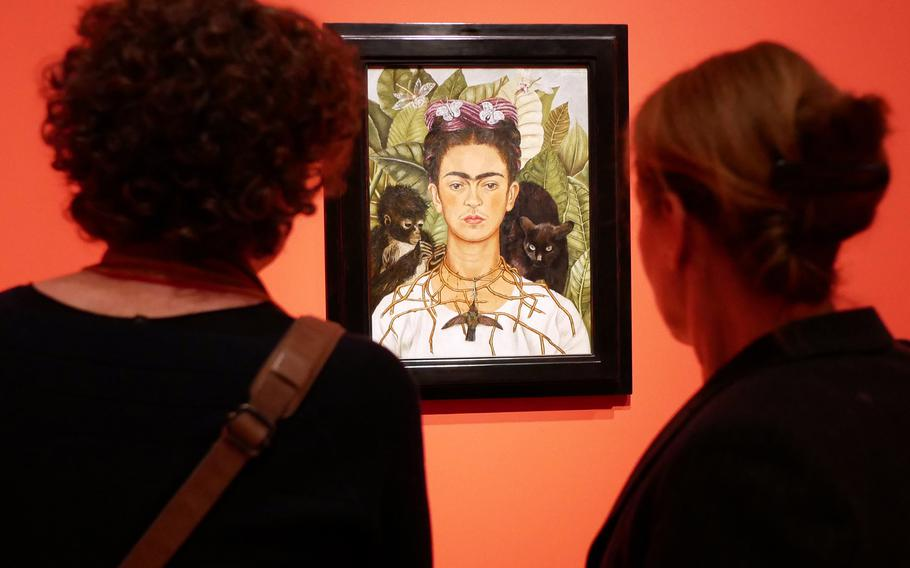 """Two visitors to the exhibit """"Fantastic Women"""" look at Frieda Kahlo's """"Self-Portrait with Thorn Necklace and Hummingbird,"""" probably the exhibit's most famous piece. The program runs through July 5 at the Schirn exhibit hall in Frankfurt, Germany."""