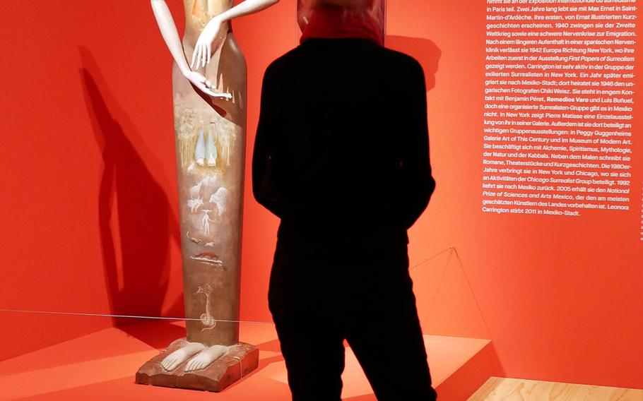 """A visitor to the exhibit """"Fantastic Women,"""" at the Schirn exhibit hall in Frankfurt, Germany, checks out Leonora Carrington's """"Le Grand Dame (Cat Woman),"""" a piece she did with the sculptor Jose Horna."""