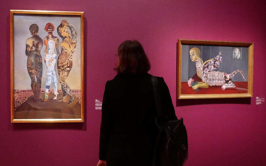 """A visitor to the exhibit """"Fantastic Women"""" at the Schirn in Frankfurt, Germany, looks at Jane Graverol's """"The Massacre of the Innocents."""" At right is """"The School of Vanity."""" The exhibit runs through July 5."""