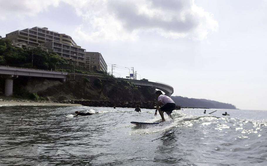 A surfer rides a wave at Yugawara Beach in Kanagawa prefecture, Japan.