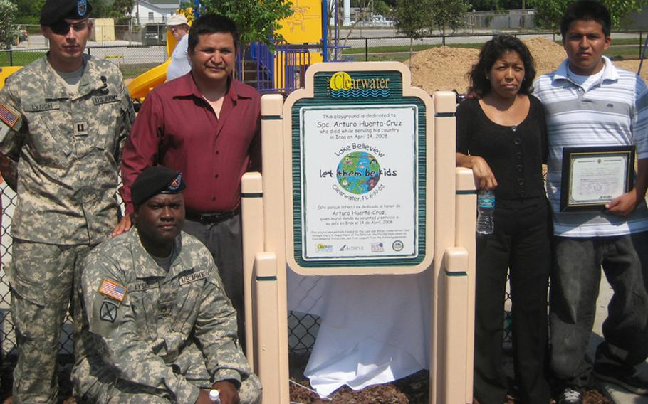 Maj. Andrew Lynch, left, then a captain, attends a playground dedication ceremony with the family of Spc. Arturo Huerta-Cruz, who was killed by the same blast that injured Lynch's right eye. Lynch lost the eye and suffered a tramatic brain injury in the April 2008 attack. He remains on active duty. The playground was dedicated in the name of Huerta-Cruz.