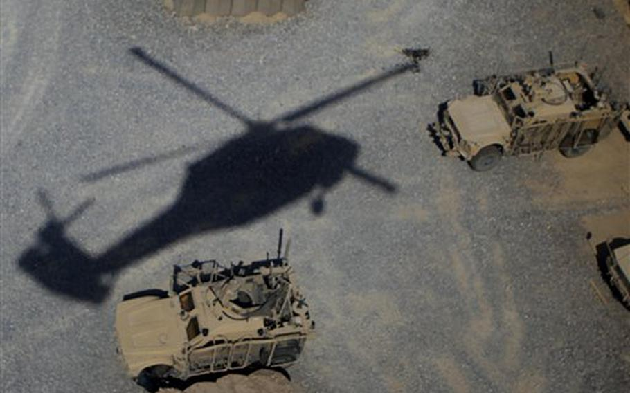 The shadow of a helicopter is shown as the aircraft comes in for a landing on the outskirts of Kandahar, Afghanistan, on Aug 5, 2011.