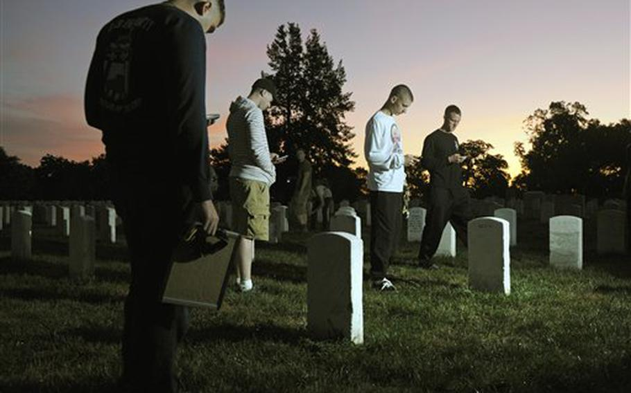 The sun rises over Section 15 as soldiers from the Army Old Guard use iPhones to photograph headstones at Arlington National Cemetery in Virginia on Aug. 24, 2011.
