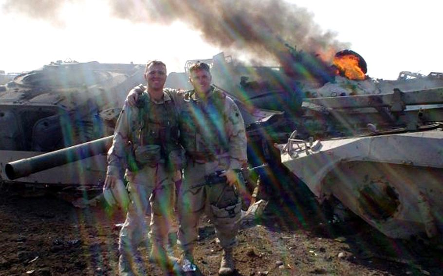 During the Iraq invasion, Stephen Kraft, right, and his Army buddy Clint Auschwitz pose in front of an inoperable tank in an Iraqi junkyard that their unit had just destroyed to keep enemy fighters from using the tank rounds as improvised explosive devices.