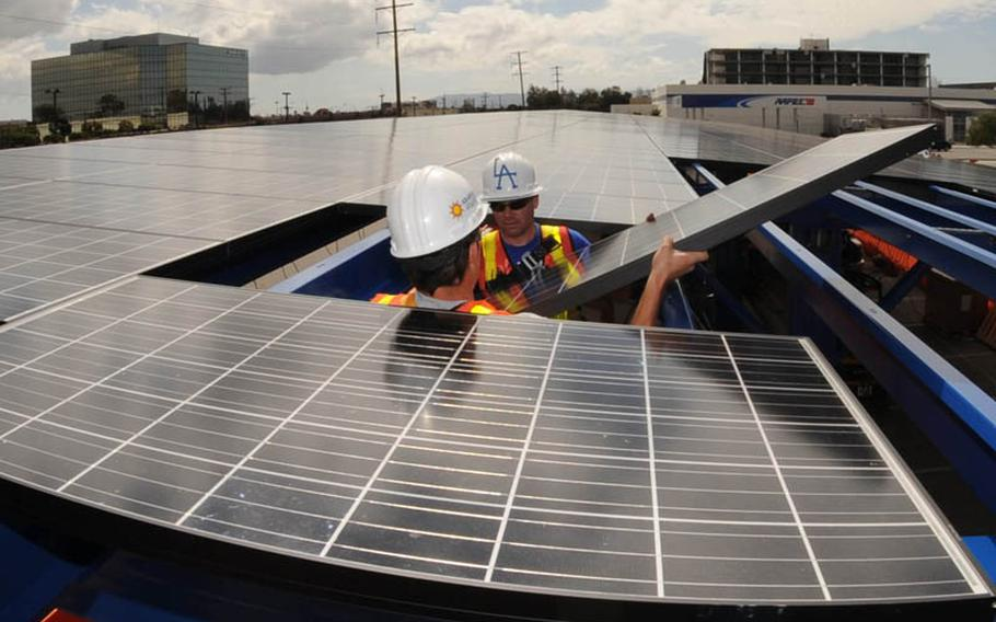 Workers install solar panels on a roof at Los Angeles Air Force Base that will help power an all-electric vehicle fleet debuting next year.