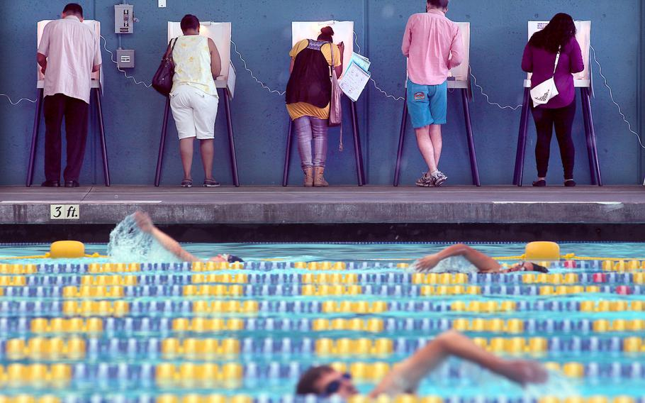 Voters cast their ballots as swimmers take laps at Echo Park Pool on Tuesday, November 6, 2012, in Los Angeles, California.