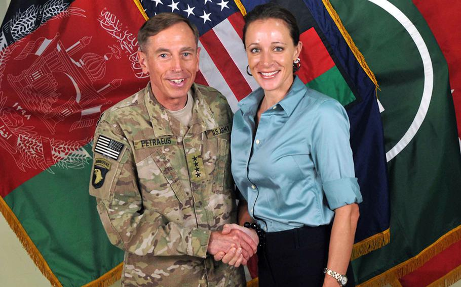 Gen. David Petraeus shakes hands with Paula Broadwell, co-author of his biography, on July 13, 2011.