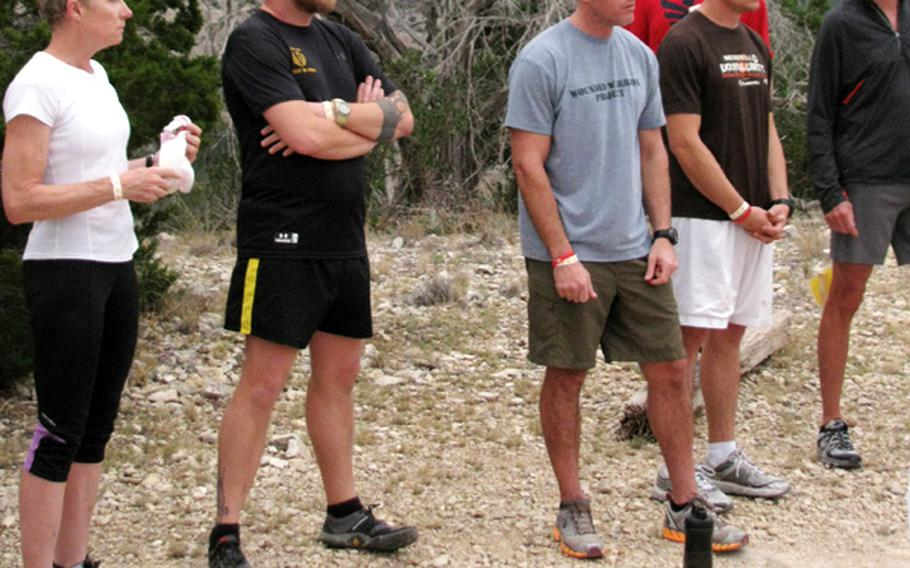 Army veteran Jim Buzzell (second from left) and other participants at Team Red, White & Blue's November running camp pause to listen to instructors before a three-mile training session.