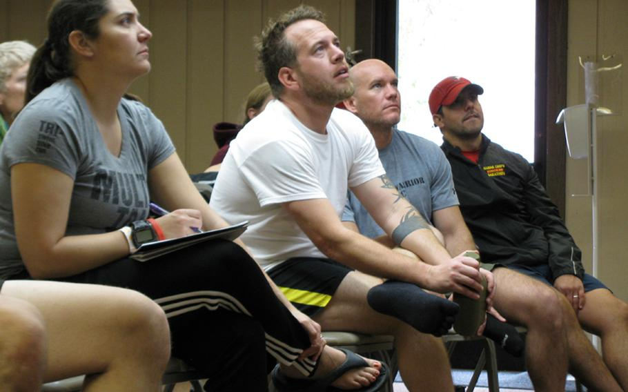 Maj. Dana Riegel (left), Army veteran Jim Buzzell (second from left) and other participants at Team Red, White & Blue's November running camp get tips on preventing common knee and back injuries.