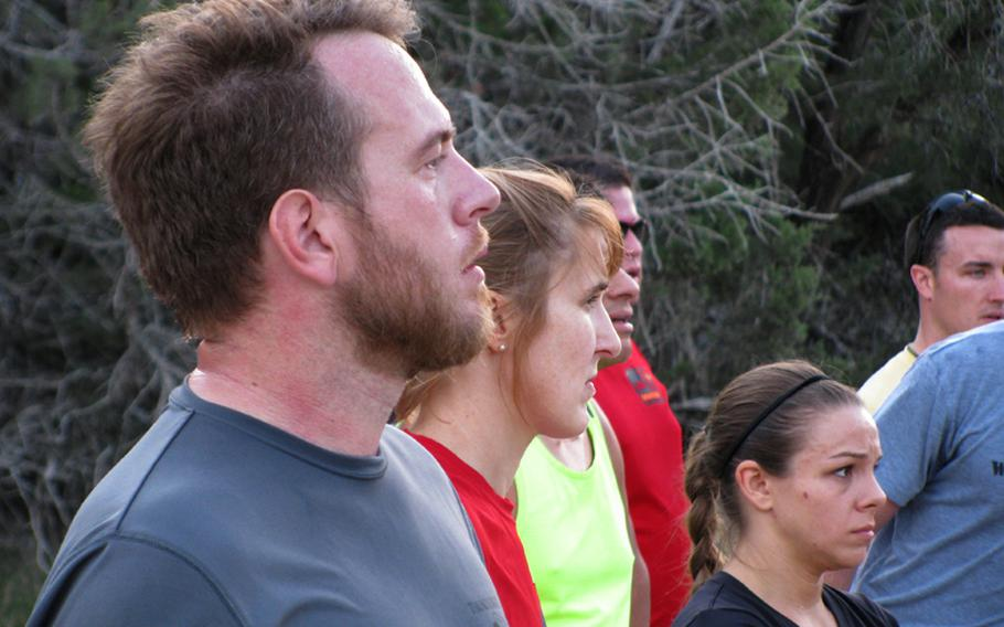 Army veteran Jim Buzzell and other participants at Team Red, White & Blue's November running camp pause to listen to instructors before a training session.