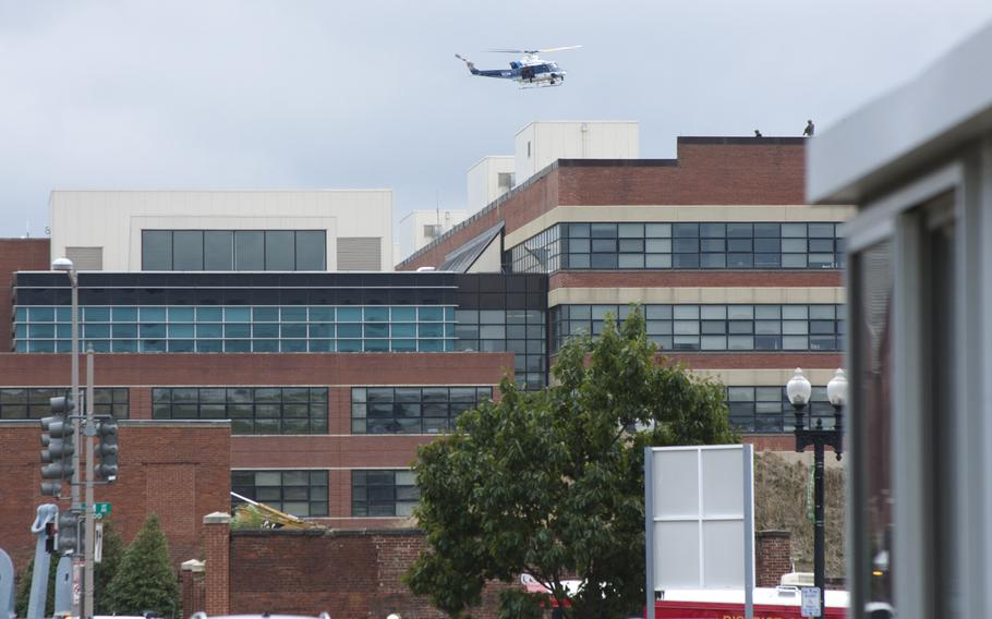 A U.S. Park Police helicopter circles over a building at Washington Navy Yard after a shooting rampage left 12 victims dead on Sept. 16, 2013.