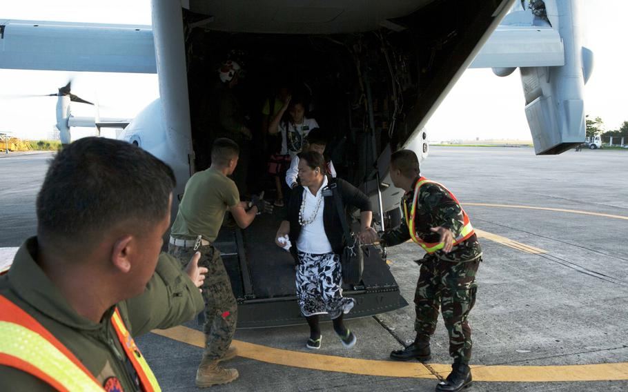 U.S. Marines guide a Filipino woman off an MV-22B Osprey and toward the terminal at Villamor Air Base Nov. 12, 2013. Typhoon Haiyan, the strongest typhoon recorded to make landfall has displaced hundreds of thousands in the Philippine Islands.