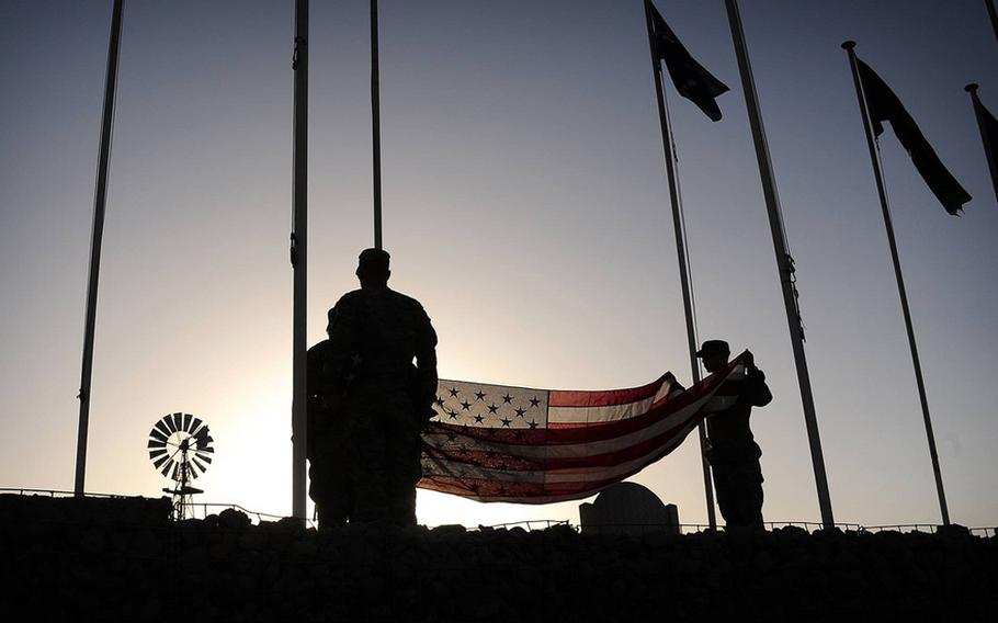 Soldiers with the California Army National Guard prepare to raise the American flag at Multinational Base Tarin Kowt in the Uruzgan province of Afghanistan, Aug. 5, 2013.