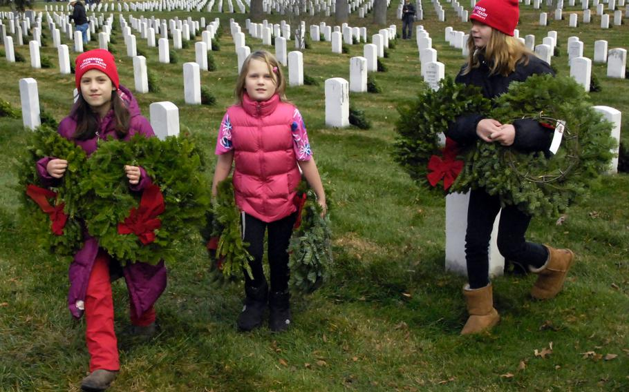 Young volunteers carry wreaths to graves at Arlington National Cemetery during a Wreaths Across America event on December 15, 2012.