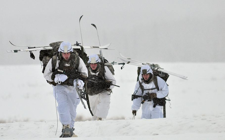 Paratroopers assigned to the 1st Squadron (Airborne), 40th Cavalry Regiment, move off the drop zone after an Arctic airborne operation in the complete over-white uniform on Malemute Drop Zone at Joint Base Elmendorf-Richardson, Alaska, Dec. 12, 2013.