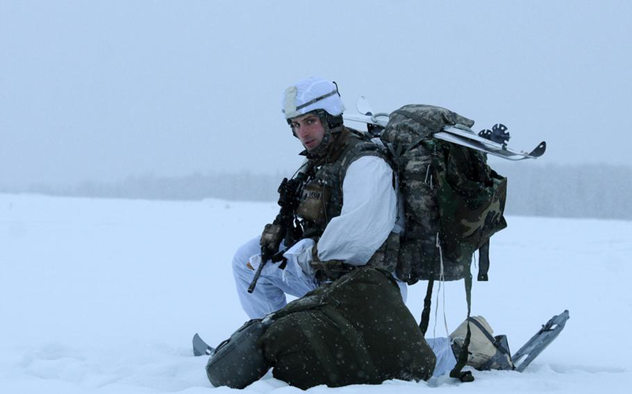 First Lt. David Pearson with 4th Infantry Brigade Combat Team (Airborne), 25th Infantry Division, waits for another paratrooper to secure his equipment after their parachute jump from a C-130 Hercules on Dec. 12, 2013 at the Malemute Drop Zone at Joint Base Elmendorf-Richardson, Alaska, on Dec. 12, 2013.