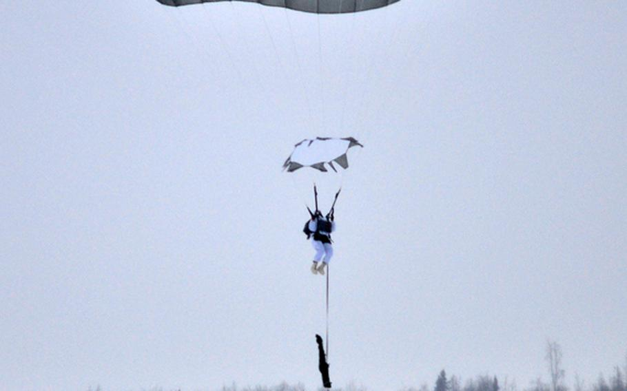 A paratrooper assigned to the 1st Squadron (Airborne), 40th Cavalry Regiment prepares for his parachute landing fall during an Arctic airborne operation in the over-white uniform on Malemute Drop Zone at Joint Base Elmendorf-Richardson, Alaska, Dec. 12, 2013. The unit is part of U.S. Army Alaska's 4th Infantry Brigade Combat Team (Airborne), 25th Infantry Division. This is the first Arctic airborne operation for the brigade since its redeployment from Afghanistan last year.