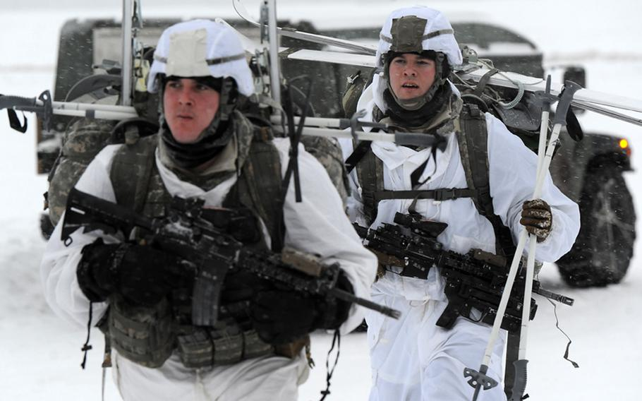 Army Sgt. Matthew Berg, a native of Prior Lake, Minn., left, and Spc. William Baker, of Midlothian, Va., both assigned the C Troop 1st Squadron (Airborne), 40th Cavalry Regiment, 4th Infantry Brigade Combat Team (Airborne), 25th Infantry Division, part of U.S. Army Alaska, march to a rally point after conducting an Arctic airborne operation in the complete over-white uniform on Malemute drop zone at Joint Base Elmendorf-Richardson, Alaska, Dec. 12, 2013.