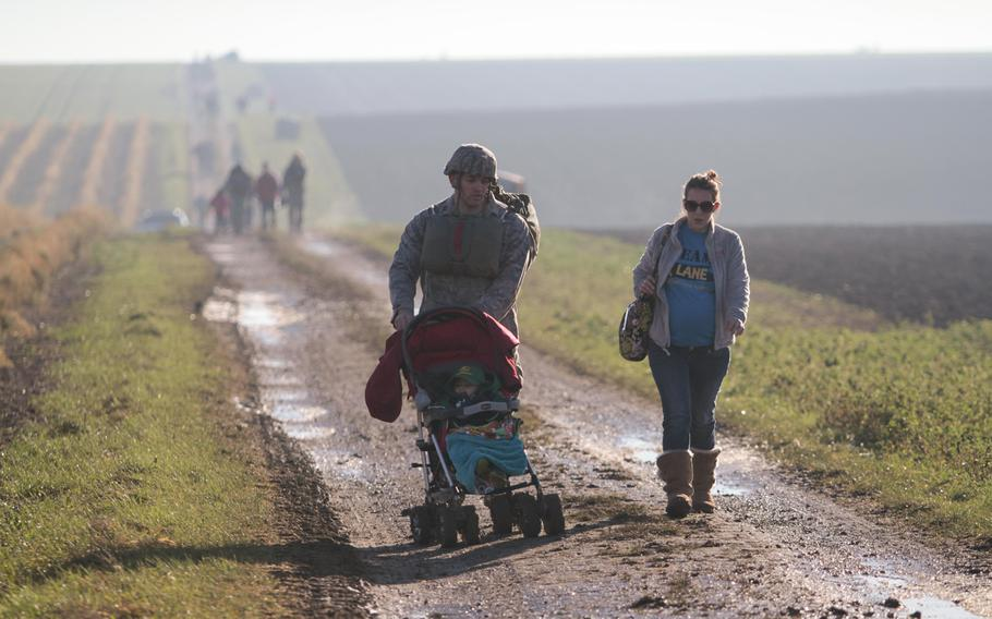 After parachuting onto a farmer's field Monday, Dec. 16, 2013, outside the German town of Alzey, Capt. Michael Wetlesen of the Air Force's 435th Contingency Response Group was met by his wife, Samantha, and son Michael Jr., whom he pushed back to the rally point in his stroller.