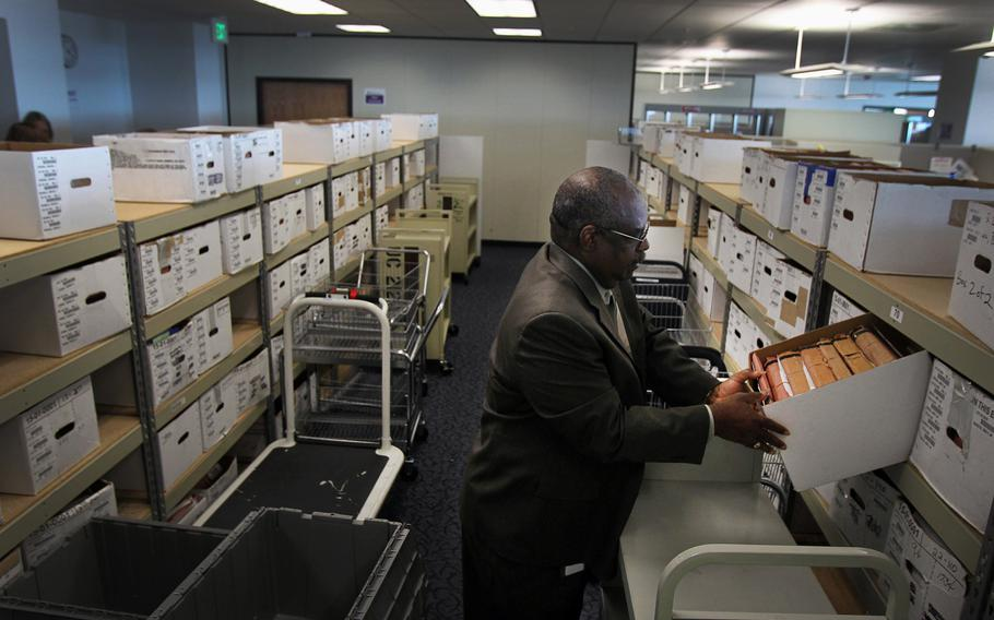 Douglas Bragg, the director of the Veterans Benefits Administration office in Oakland, Calif., looks into one of the many boxes that contain the cases of veterans with pending claims, April 18, 2013.