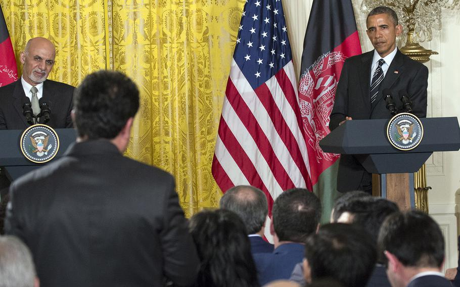 President Ashraf Ghani of Afghanistan and President Barack Obama listen to a question during a press conference at the White House, Mar. 24, 2015.