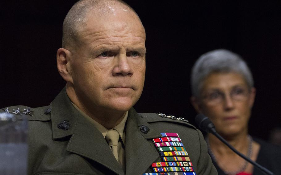 Lt. Gen. Robert Neller listens to the opening statements during a Senate Armed Services Committee hearing on his nomination to be general and Commandant of the Marine Corps, July 23, 2015 on Capitol Hill. Behind him is his wife, D'Arcy.