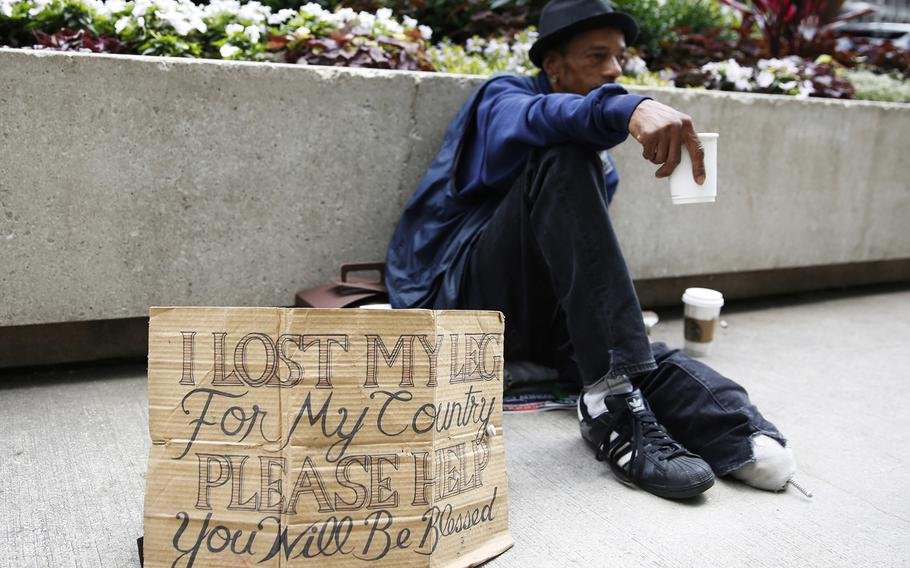 Mike Droney, a homeless veteran, displays a redesigned cardboard sign in downtown Chicago on July 2, 2015. (Michael Noble Jr./Chicago Tribune/TNS)