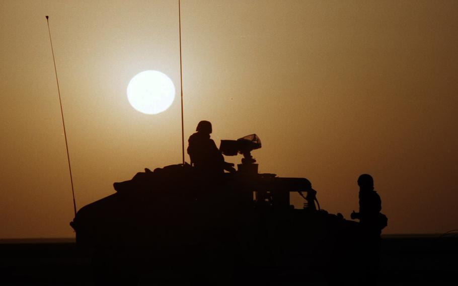 American servicemembers are silhouetted against the desert sun during the Gulf War.
