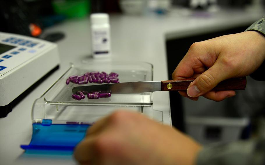 A pharmacy technician, fills a prescription at Aviano Air Base, Italy.