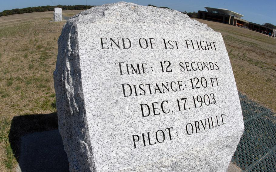 A commemorative stone at the Wright Brothers National Memorial in Kitty Hawk, N.C. In the background are the visitors center on the right and the stone marking the endpoint of the second flight on the left.