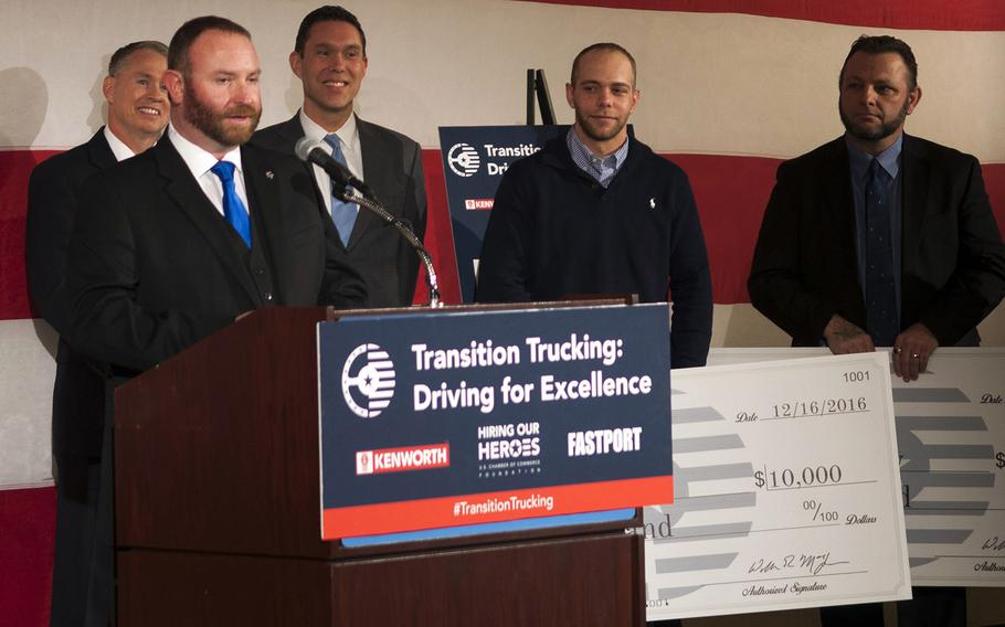 Navy veteran Troy Davidson addresses a crowd inside the U.S. Chamber of Commerce Foundation after being announced the winner of a $150,000 Kenworth semi-truck Friday, Dec. 16, 2016. Kevin Scott, an Army veteran, and Russell Hardy, a veteran of the Army and Navy, stand behind Davidson holding $10,000 checks they were awarded as runners-up in the competition, put on by Hiring our Heroes, Kenworth and FASTPORT.