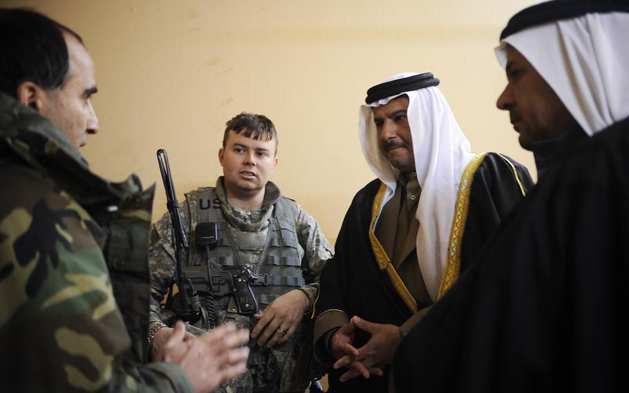 In a 2008 file photo, an interpreter, left, translates for U.S. Army Capt. Matthew Schlosser, 1st Battalion, 8th Infantry Regiment, Fort Carson, Colo., during a meeting with sheiks at an Iraqi police station in Nimrud, Iraq.