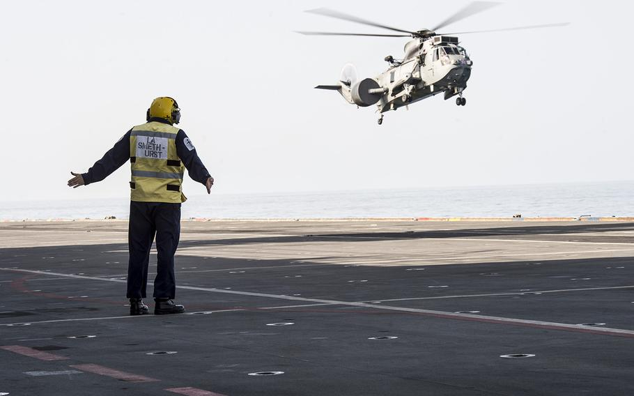 A flight deck crew member aboard the Royal Navy helicopter carrier HMS Ocean directs a Sea King MK7 airborne surveillance and control helicopter landing on the ship during exercise Unified Trident in the Persian Gulf Jan. 31, 2016.    Chris Church/Stars and Stripes