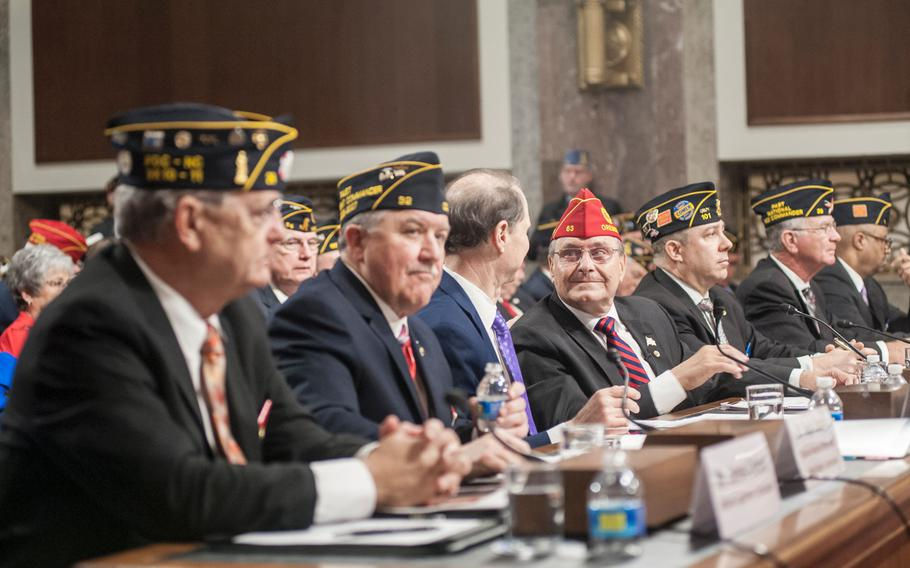 American Legion National Commander Charles Schmidt, center, looks at Sen. Ron Wyden, D-Oregon, before the start of a presentation on Capitol Hill on Wednesday, March 1, 2017, as members of Congress heard from American Legion representatives on issues that are of concern to military veterans.
