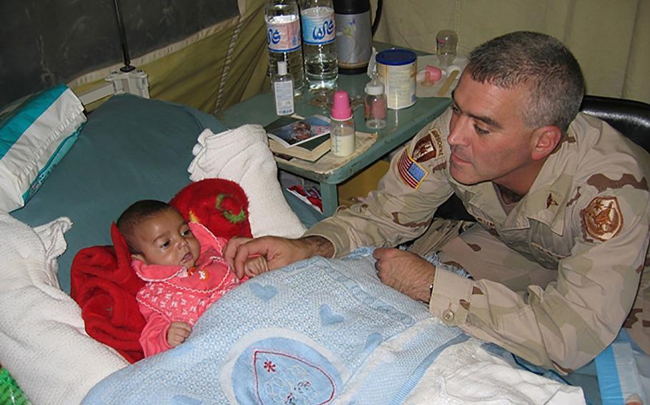 Maj. Brad Wenstrup, chief of surgery at the Abu Ghraib Hospital, plays with Tabark Addul Rahman, aka Baby Tabitha on Oct. 30, 2005.