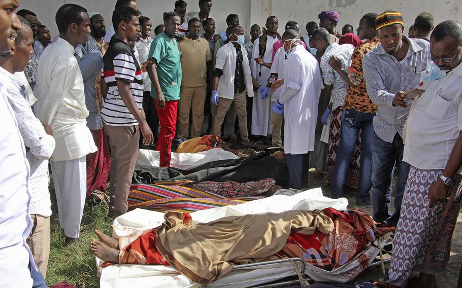 Somalis observe bodies which were brought to and displayed in the capital Mogadishu, Somalia Friday, Aug. 25, 2017.