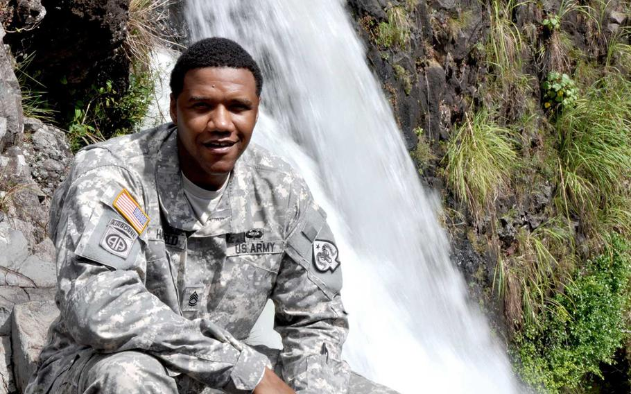 In this June 6, 2015 photo, U.S. Army National Guard Sgt. 1st Class Charleston Hartfield of the 100th Quartermaster Company poses for a photo at Rainbow Falls near Hilo, Hawaii. Hartfield was one of the people killed in Las Vegas after a gunman opened fire on Sunday, Oct. 1, 2017, at a country music festival.