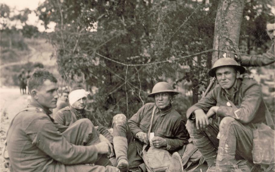 Allied soldiers, one with a bandaged head, sitting on the ground during World War I.