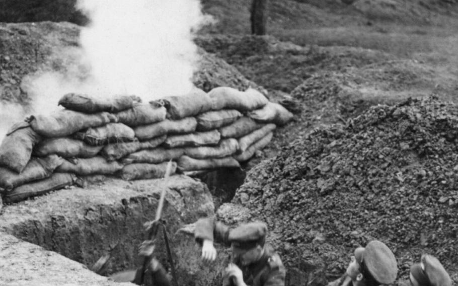 Three British soldiers in trench under fire in August 1916, during World War I.