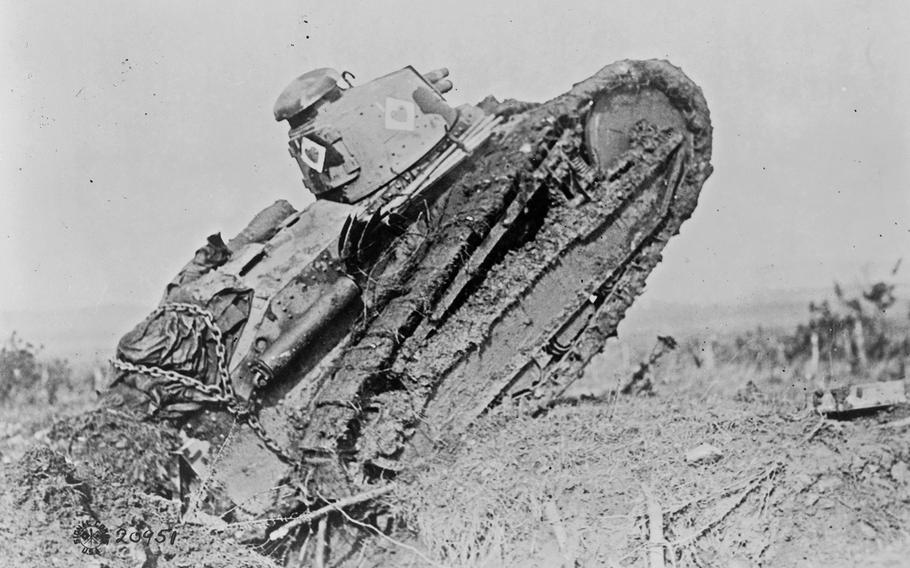 A tank ploughing its way through a trench and starting toward the German line, during World War I, near Saint Michel, France.