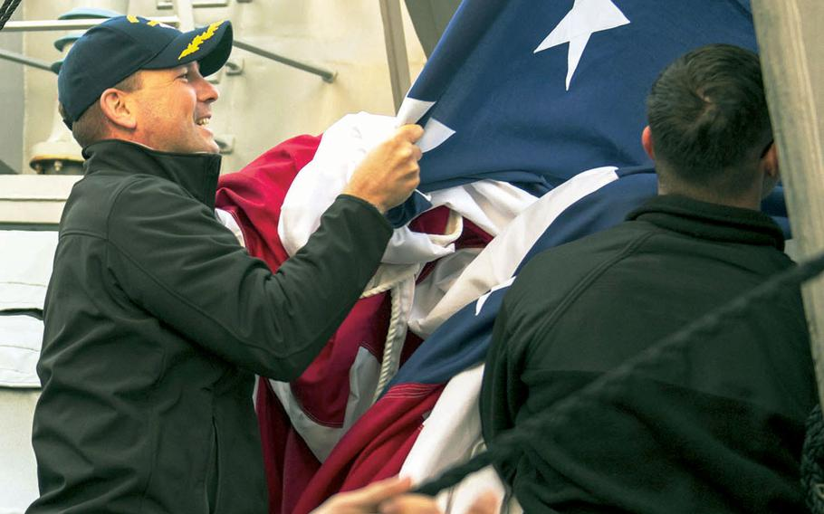 Cmdr. Bryce Benson brings down the ensign while serving aboard the destroyer USS Fitzgerald in the Pacific Ocean as the ship's executive officer in February 2016.