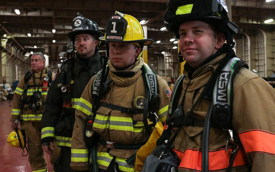 Firefighters wait their turn to go below deck of the cargo ship Cape Rise to combat a simulated fire on May 17, 2018. The firefighters were participating in the 27th annual Marine Firefighting School held May 14-19 in Norfolk, Va.