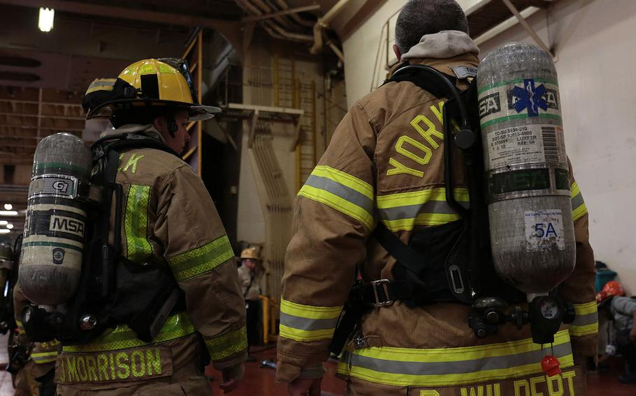 Firefighters gear up to go below deck of the cargo ship Cape Rise to combat a simulated fire on May 17, 2018. The firefighters were participating in the 27th annual Marine Firefighting School held May 14-19 in Norfolk, Va.